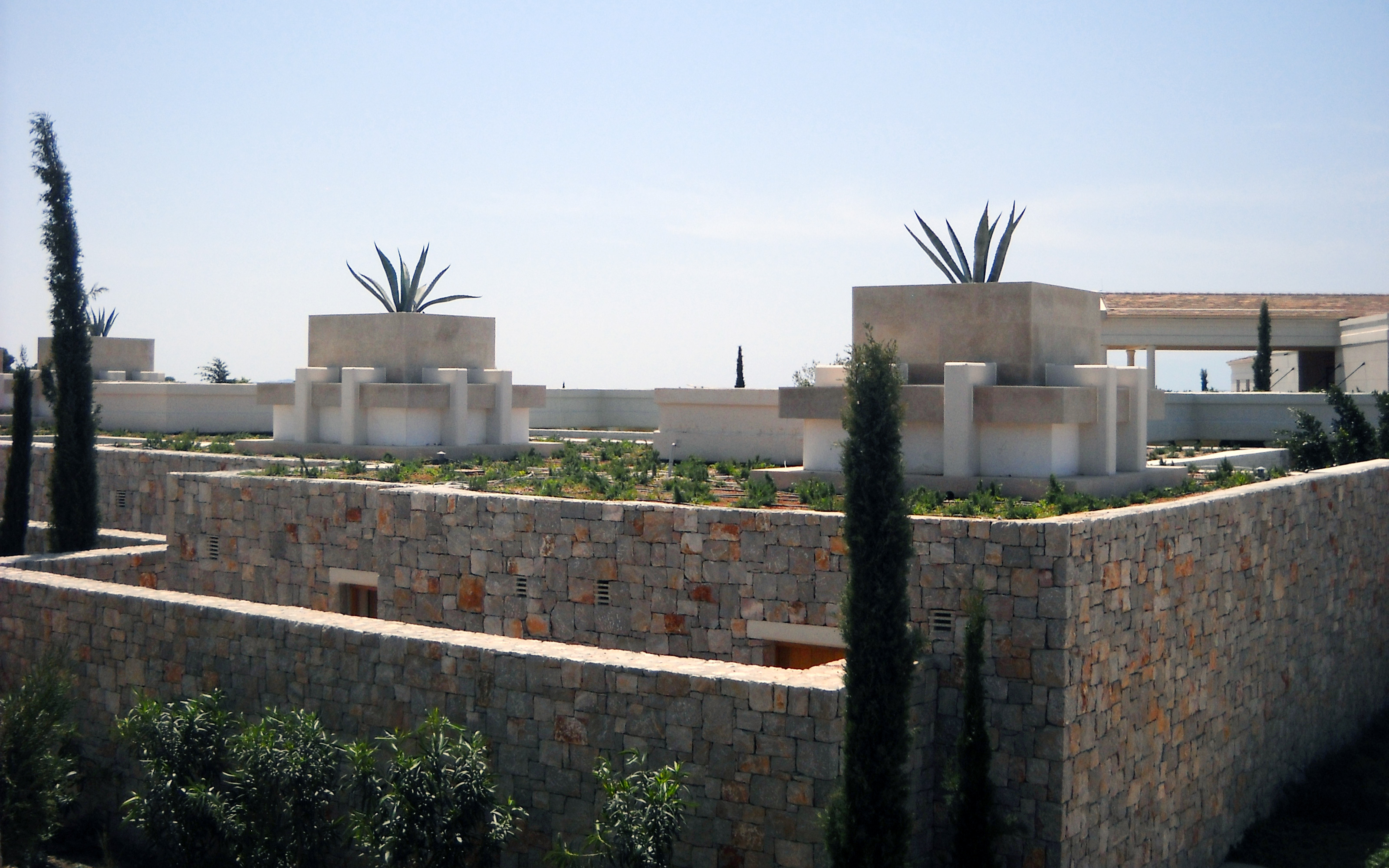 Stone houses with green roofs and Agaves