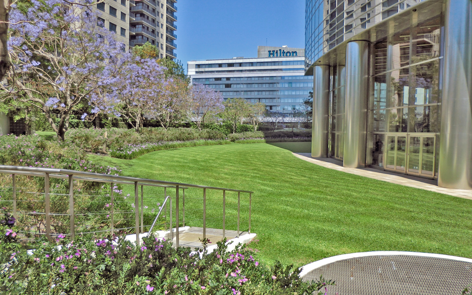 Park with lawn, flowering Jacaranda trees and entrance to the underground garage