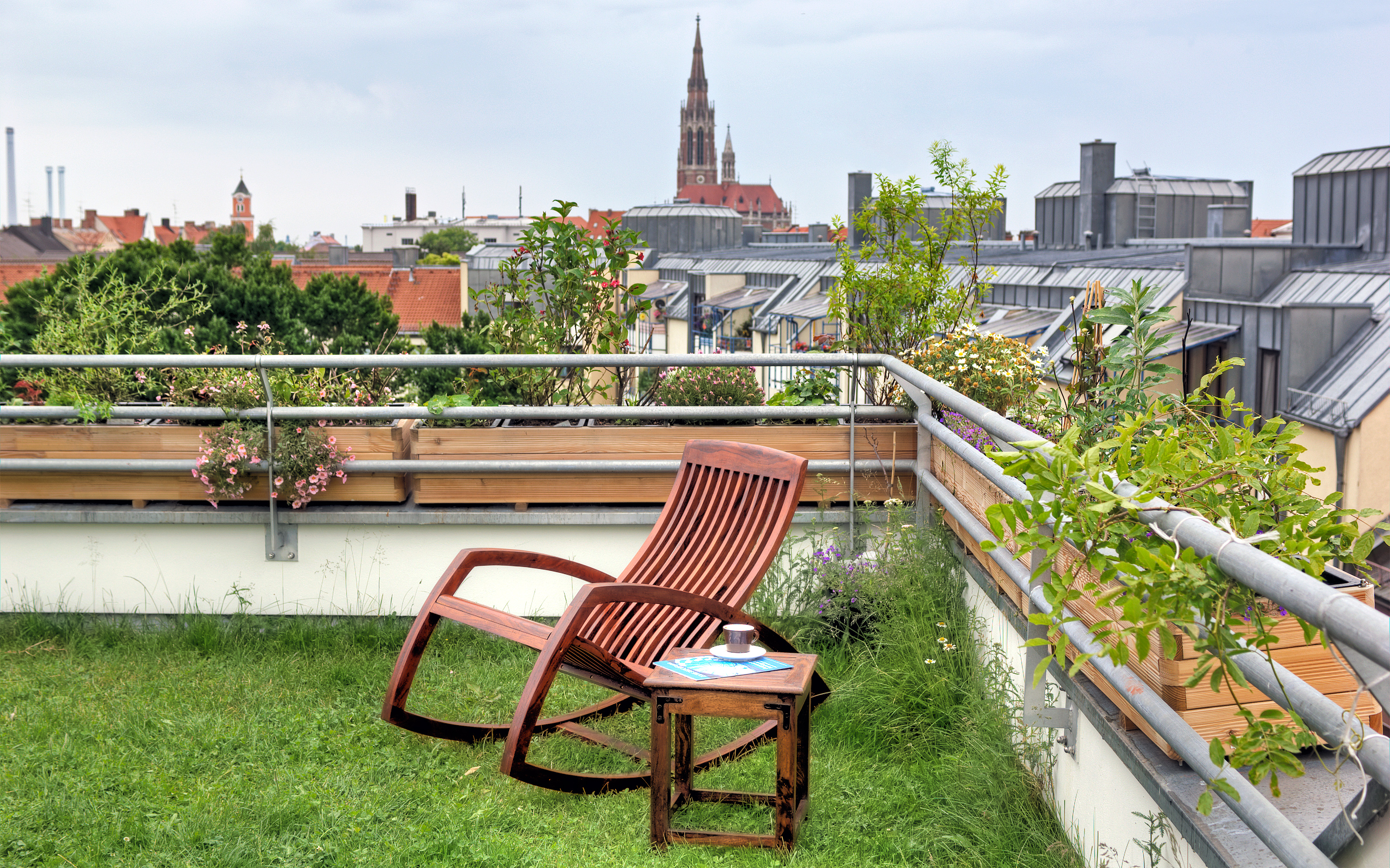 Rocking chair on a roof garden with lawn in the city