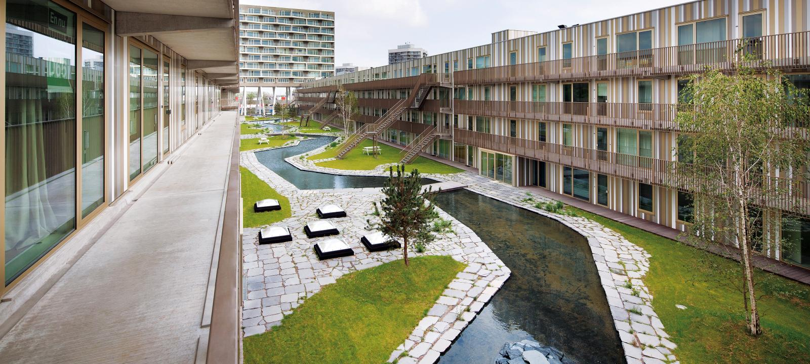 Water course and lawn with small trees, surrounded by apartment buildings