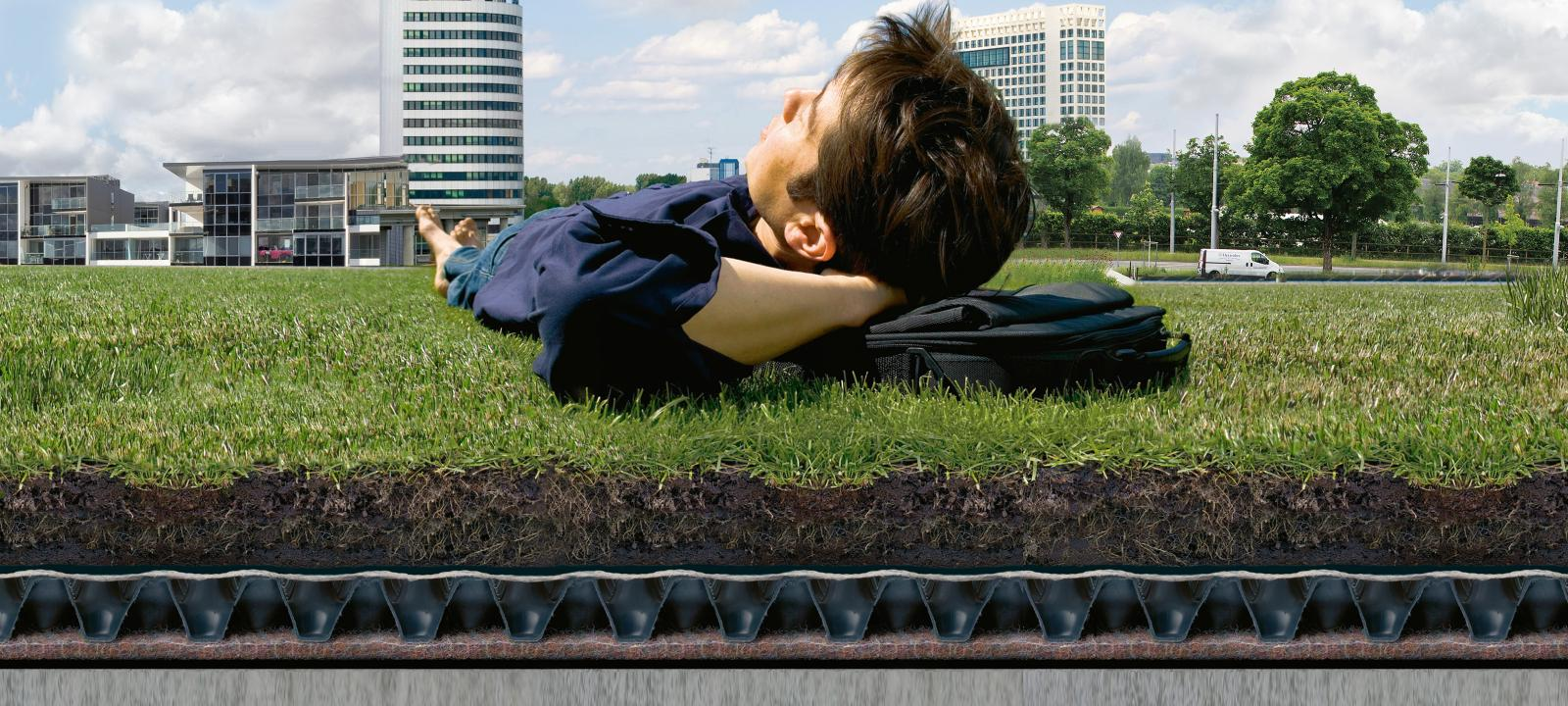 Man relaxing on a lawn established on a green roof system build-up