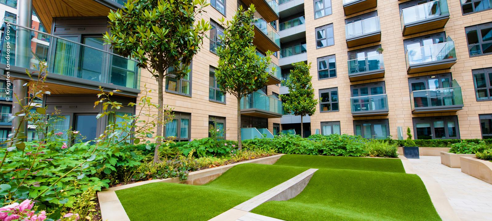 Lawn, small trees and plant beds surrounded by apartment blocks