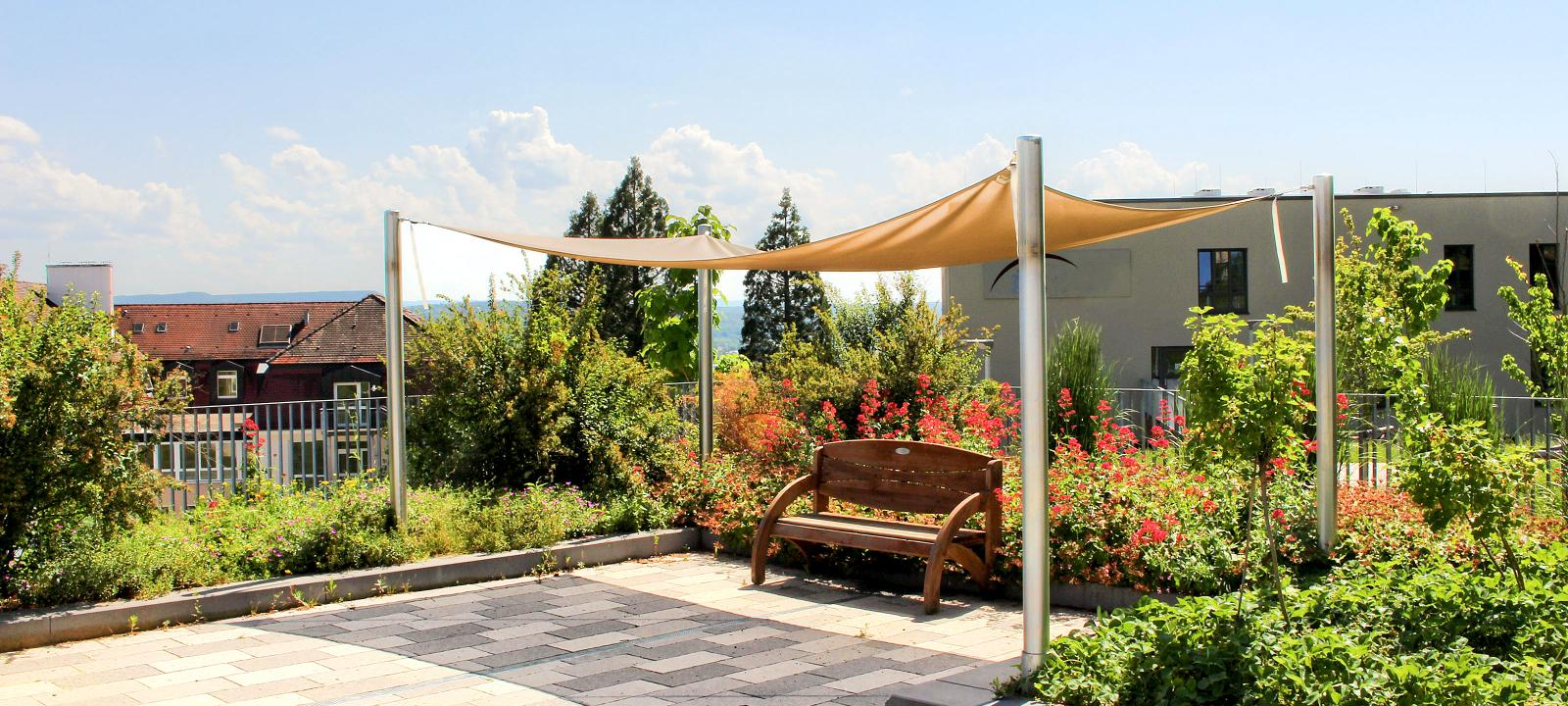 Roof garden with shrubs, perennials and bench on paved terrace