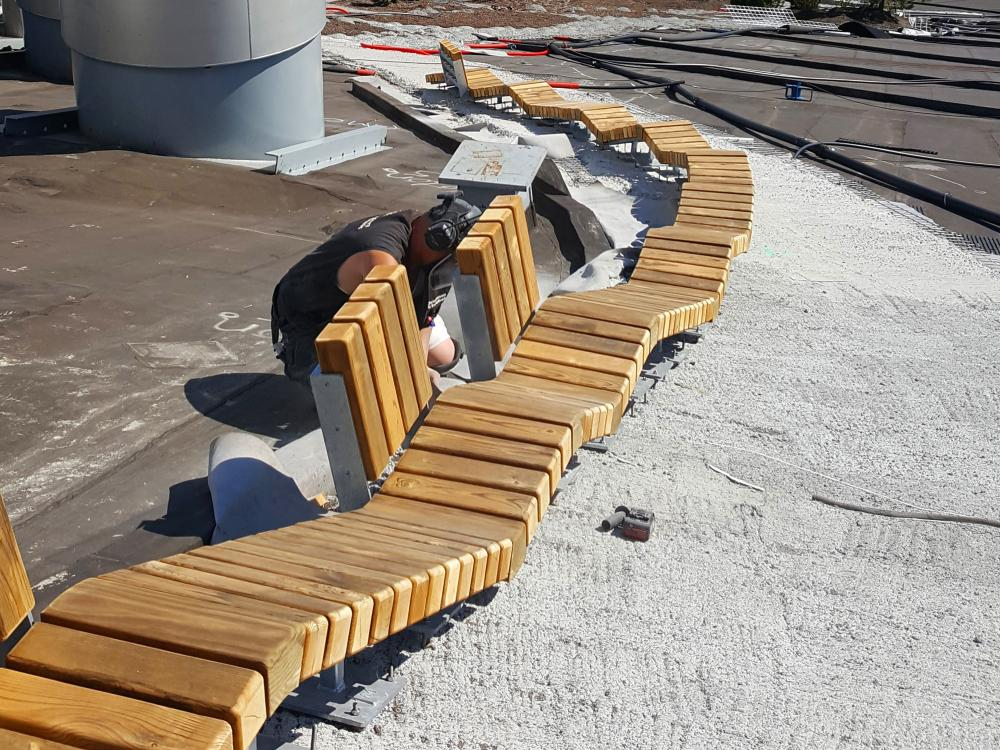 Wooden benches being constructed on a pitched roof