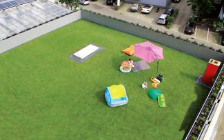 Lawn and playground for children on a rooftop