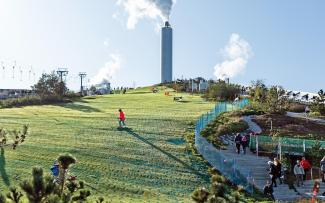 People skiing on synthetic mats on a pitched green roof