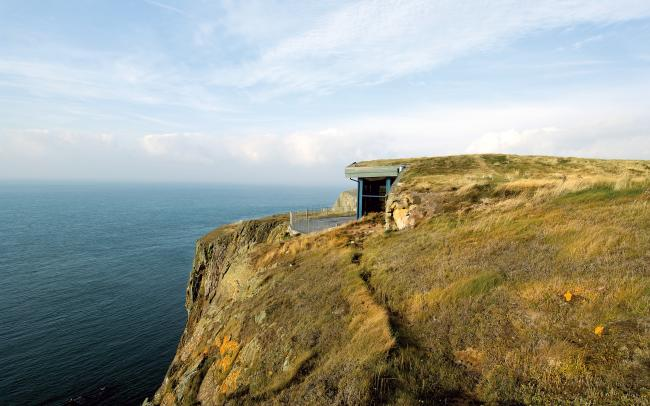 Building with green roof on cliff