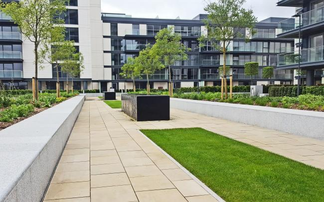 Pathways, lawn and planting beds surrounded by residential buildings